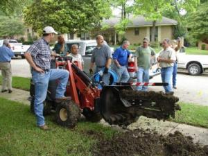 Delray Beach sprinkler installation team with a trencher